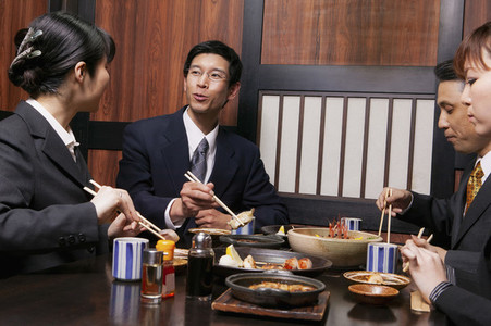 Business people eating lunch with chopsticks at restaurant table