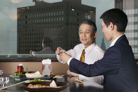 Japanese businessmen drinking with lunch in highrise restaurant