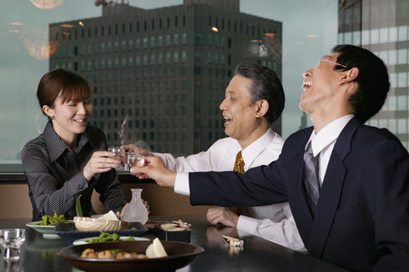 Happy business people toasting sake in highrise restaurant