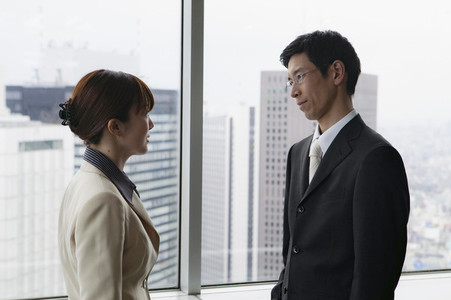 Business people talking face to face in urban highrise office window