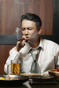 Businessman smoking cigar at lunch in restaurant
