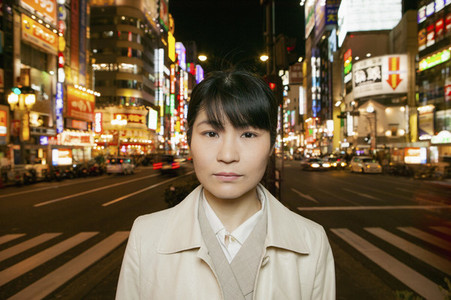 Portrait serious businesswoman on city street at night Tokyo Japan