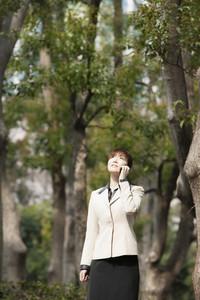 Businesswoman talking on smart phone below trees in park
