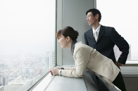 Business people looking out highrise office window