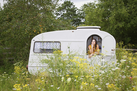 Young woman relaxing inside camper trailer in idyllic meadow