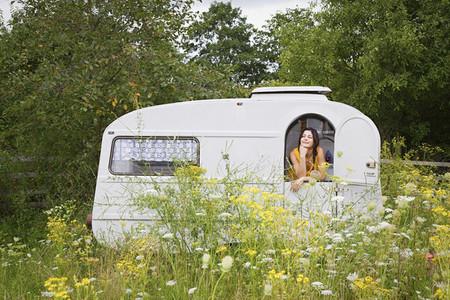 Young woman relaxing inside camper trailer in idyllic meadow
