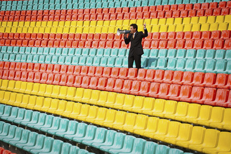 Man with megaphone in colorful soccer stadium seats