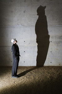 Man looking up at tall shadow on wall