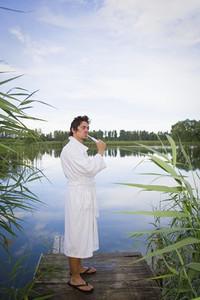 Man in bathrobe brushing teeth at tranquil lake