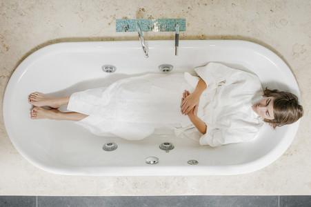 Serene young woman in bathrobe laying in empty bathtub