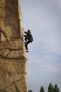 Businessman climbing steep rock face