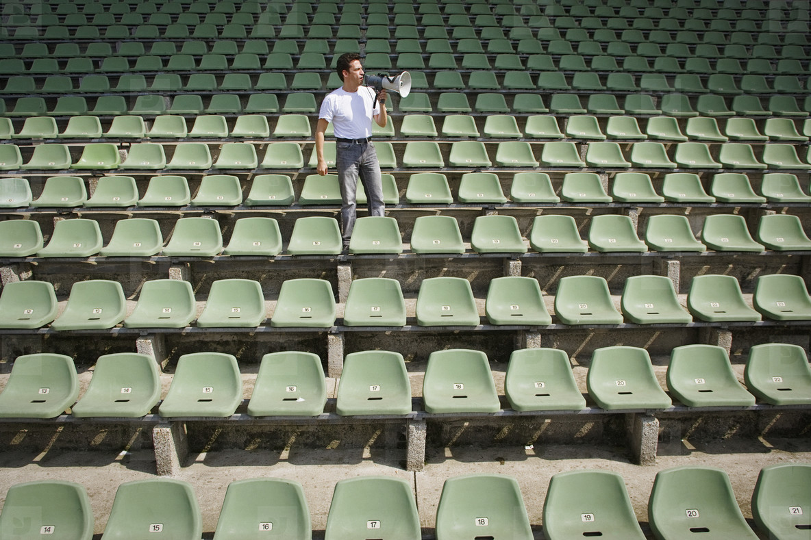 Man with bullhorn in stadium with green seats