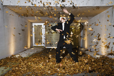 Businessman playing in autumn leaves in covered driveway