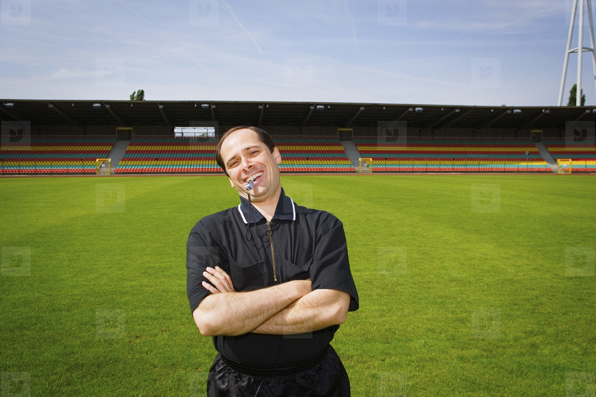 Portrait happy soccer coach with whistle on sunny pitch