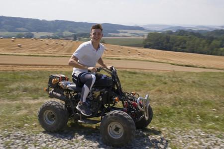 Portrait happy teenage boy riding quadbike in sunny rural field