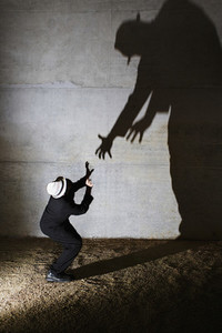 Man cowering from tall ominous shadow on wall
