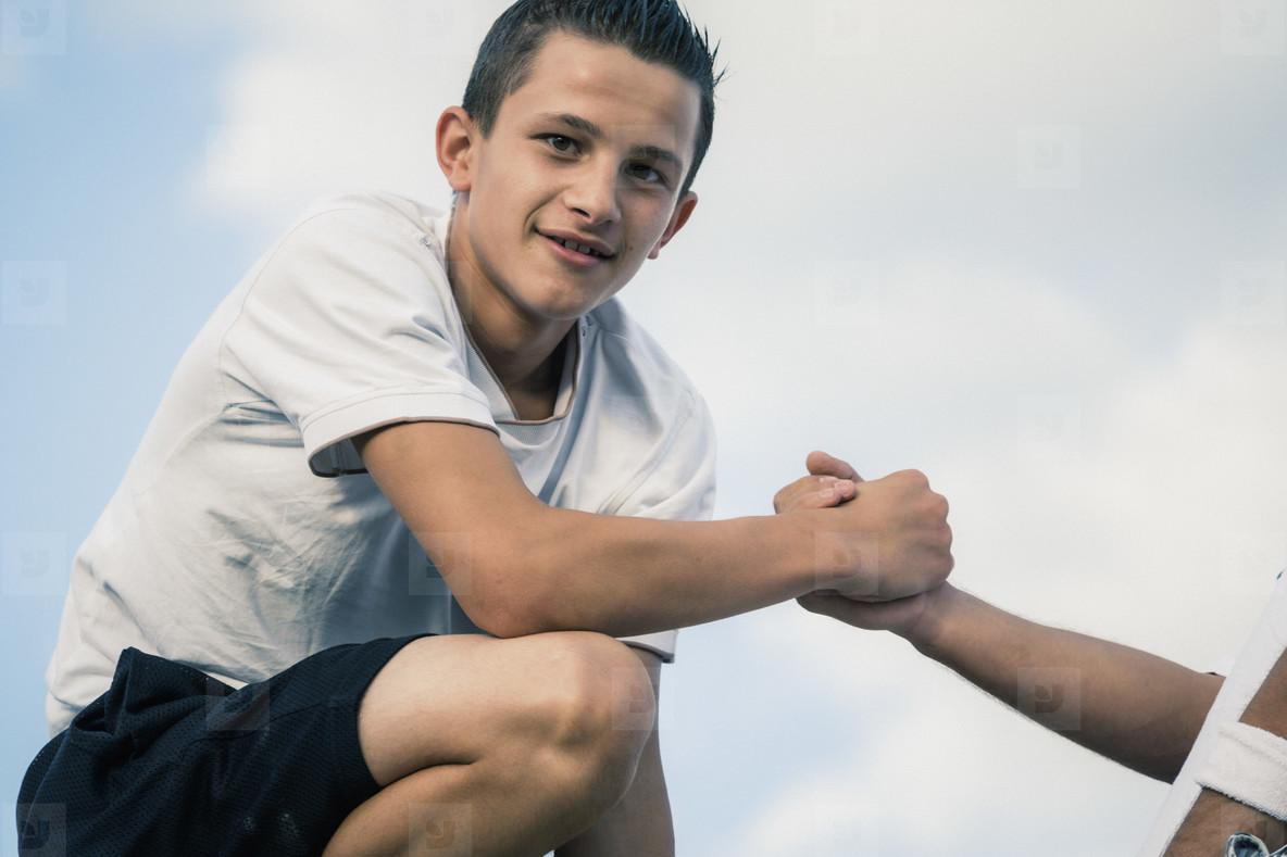 Portrait confident teenage boy holding hands with friend