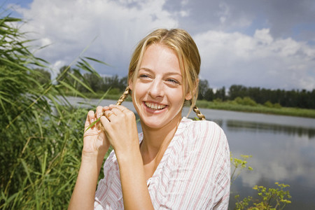 Portrait happy young woman with blonde braids at sunny lake