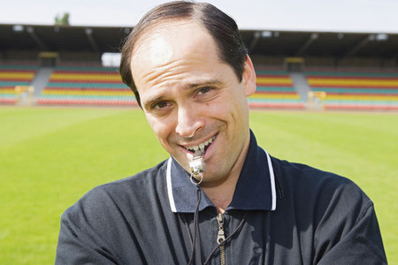 Portrait smiling confident male soccer coach with whistle on field