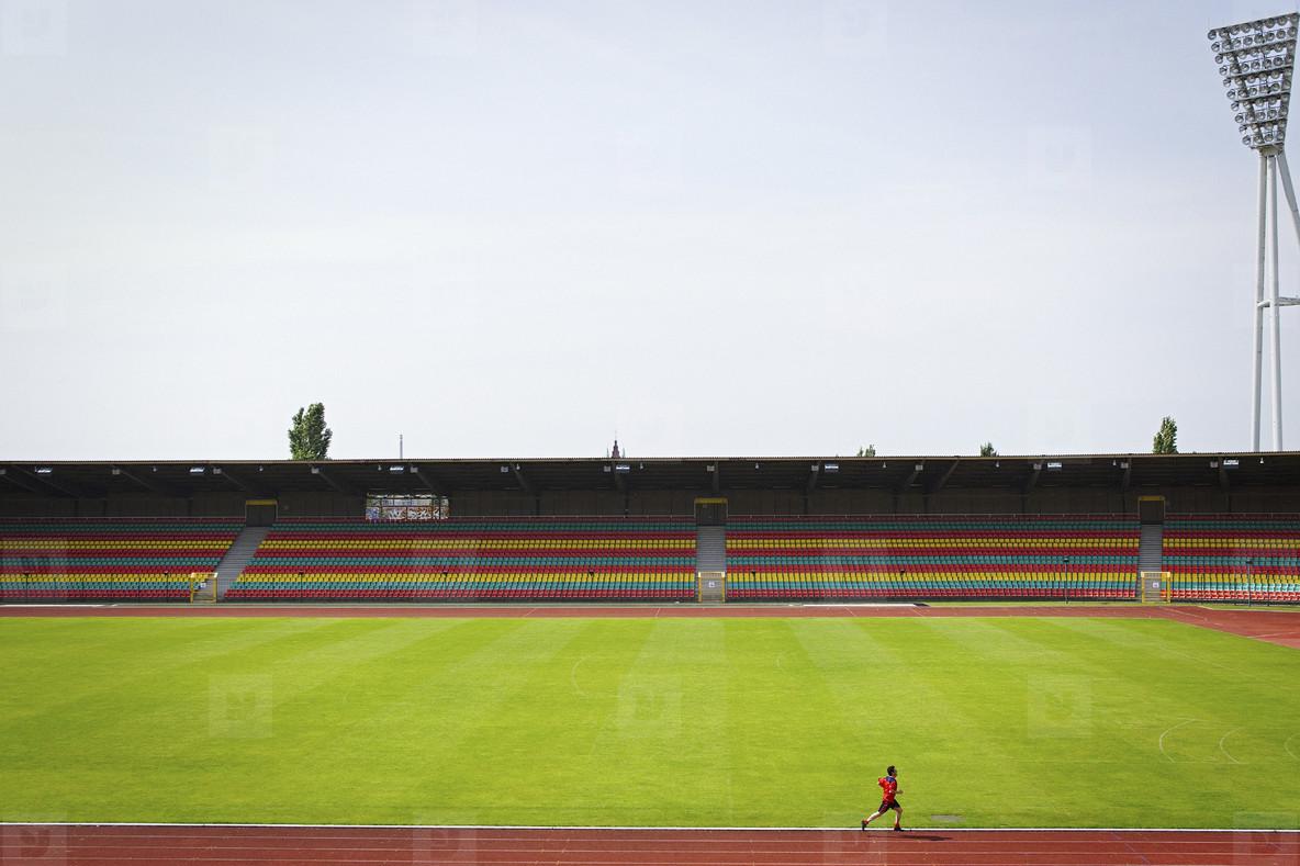 Man running on track at sunny soccer stadium