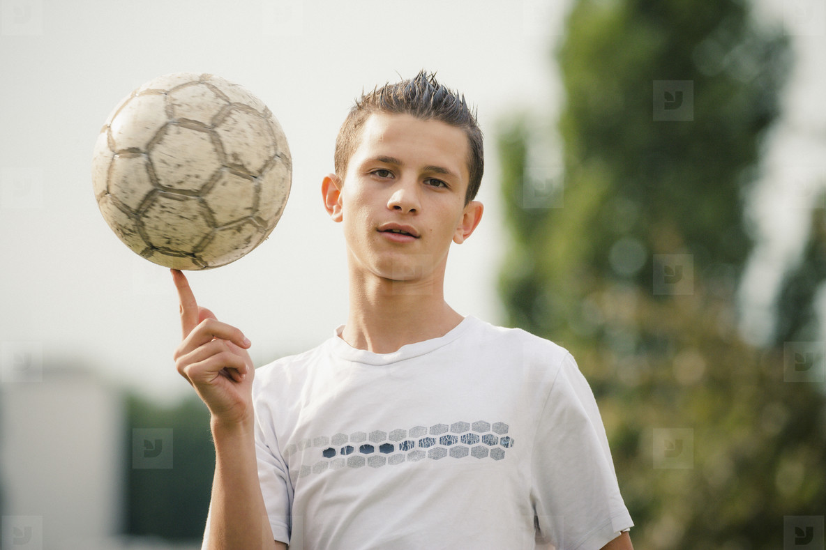 Portrait cool teenage boy spinning soccer ball on finger