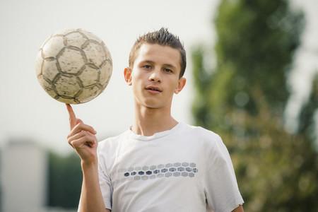Portrait cool teenage boy spinning soccer ball on finger