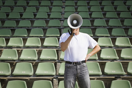 Man using bullhorn among green stadium seats