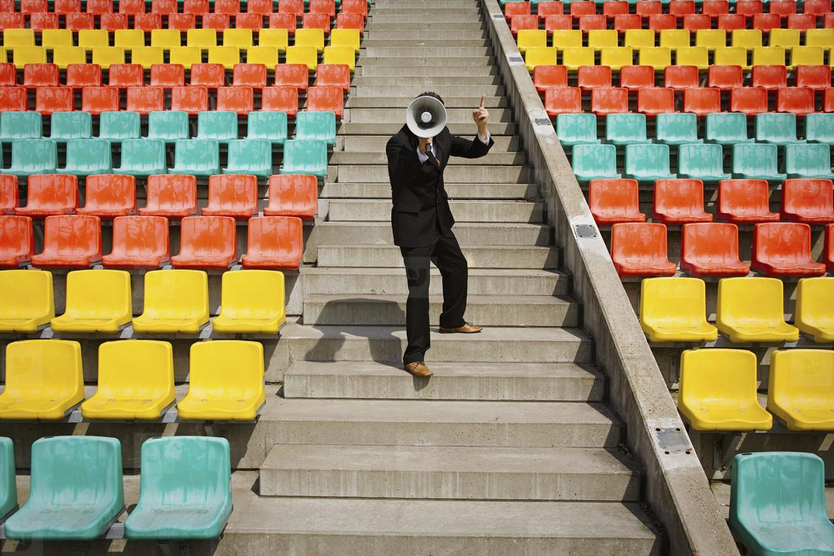 Businessman with bullhorn on sunny steps in stadium