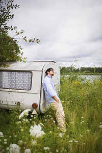 Young man at camper trailer in idyllic lakeside meadow