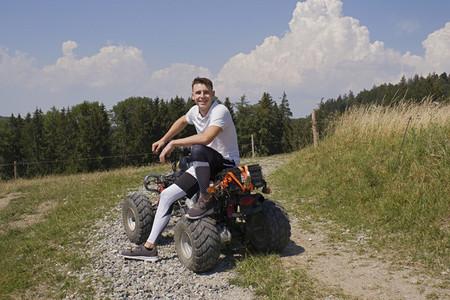 Portrait happy teenage boy on quadbike on sunny rural gravel road
