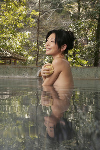 Beautiful happy young woman soaking in Onsen pool