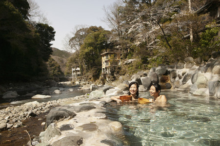 Happy young women soaking in sunny Onsen pool Izu Japan