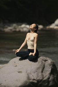 Serene beautiful young woman meditating in lotus pose on sunny rock