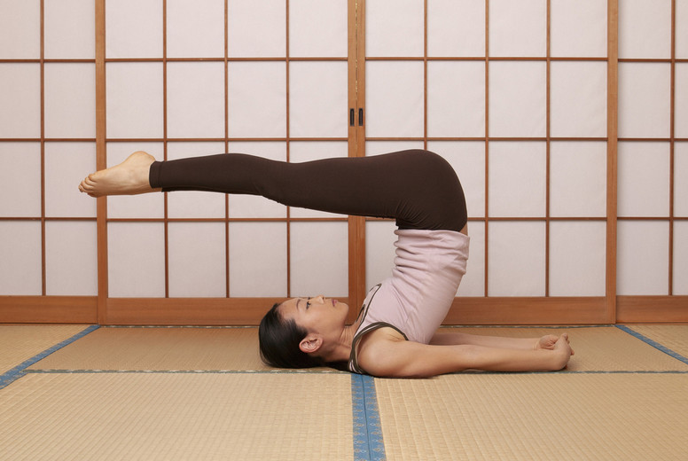 Young woman practicing yoga pose on mat