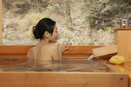 Young woman soaking in Onsen tub