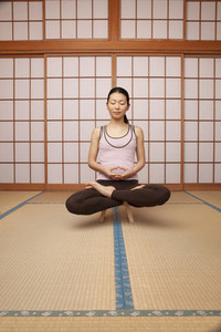 Serene young woman meditating in lotus pose on stool