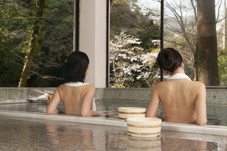 Young women relaxing in tranquil pool at Onsen