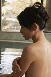 Serene nude young woman soaking in pool at Onsen