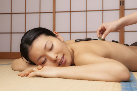 Serene young woman receiving hot stone massage at spa