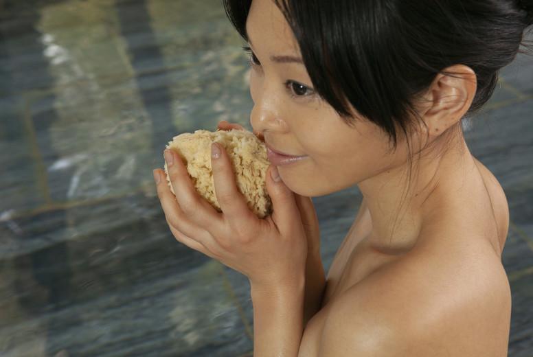 Beautiful young woman with loofah sponge in spa pool