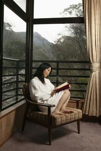 Young woman in bathrobe reading book in window corner