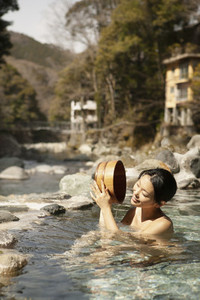 Happy young woman with bucket in sunny pool at Onsen Izu Japan