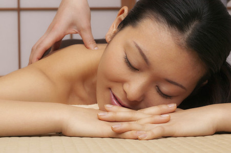 Close up serene young woman receiving massage in spa