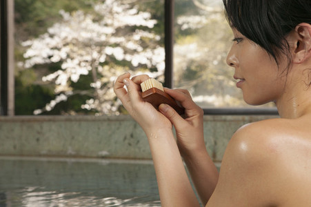 Young woman using nail brush in pool at Onsen