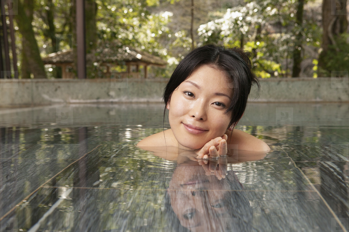Portrait beautiful young woman soaking in pool at tranquil Onsen