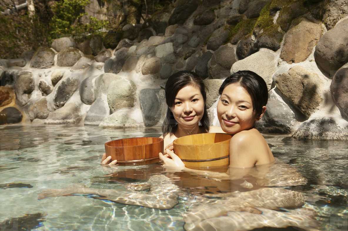 Portrait beautiful young women with buckets in pool at Onsen