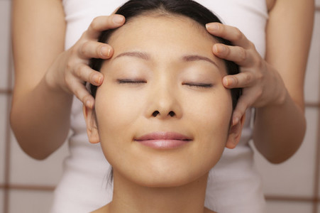 Close up serene young woman receiving scalp massage in spa