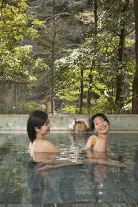 Young woman with loofah scrubbing friend039 s back in pool at Onsen