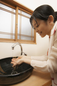 Young woman washing hands at spa sink