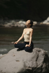 Carefree young woman meditating in lotus pose on sunny rock